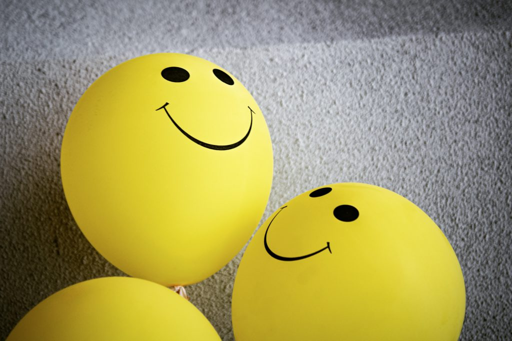Happy face balloons to celebrate small wins on the journey